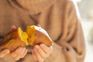 半分食べられたホットドッグを持つ手の写真・画像素材[2692955]
