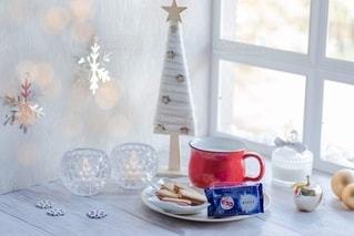 テーブルの上にコーヒーと花瓶1本の写真・画像素材[2719216]
