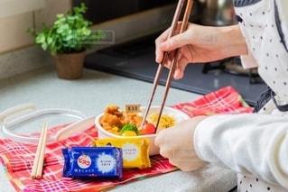 食べ物の皿をテーブルの上に置く人の写真・画像素材[2719509]