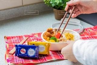 食べ物の皿を持ってテーブルに座っている人の写真・画像素材[2719510]