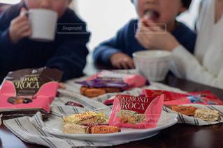 食べ物の皿を持ってテーブルに座っている人々のグループの写真・画像素材[2849372]