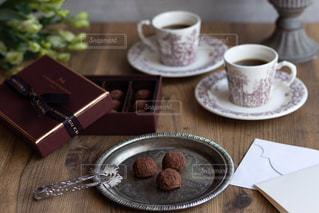 木製のテーブルの上に座っているコーヒーのカップの写真・画像素材[2895834]
