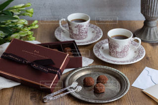 木製のテーブルの上に座っているコーヒーのカップの写真・画像素材[2895840]