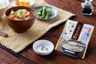 食べ物の皿と一杯のコーヒーを木製のテーブルに置いての写真・画像素材[3106059]