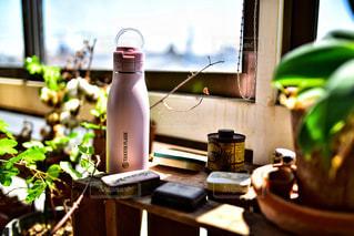 窓の横の机の上に座っている花瓶の写真・画像素材[2417226]