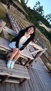木製のベンチに座っている人の写真・画像素材[1623178]