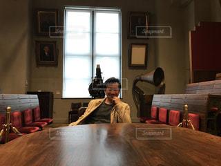 部屋のテーブルに座っている人の写真・画像素材[1653341]