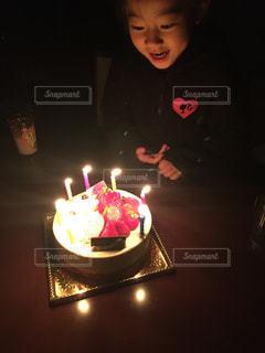 キャンドルとバースデー ケーキの前に座っている人の写真・画像素材[1667866]