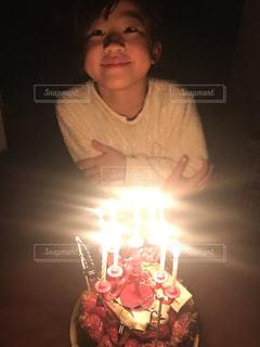 キャンドルで誕生日ケーキを持っている娘の写真・画像素材[1694734]