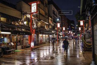 雨の夜に通りを歩いている人々のグループの写真・画像素材[2177627]