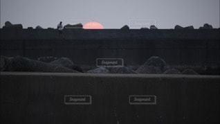 男性,1人,海,空,夕日,太陽,夕焼け,堤防,海岸,釣り人,光,釣り,夕陽,日の入り,テトラポット,テトラ