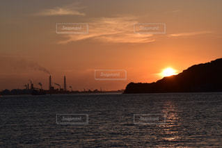 風景,海,空,夕日,屋外,太陽,雲,夕焼け,夕暮れ,船,水面,海岸,工場,山,オレンジ,光,煙,煙突,夕陽,地平線,日の入り,光の道