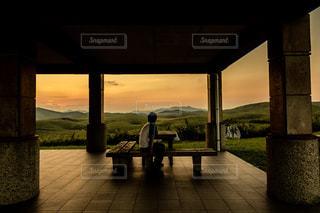 大地に沈む夕日を眺める男性の写真・画像素材[1642489]