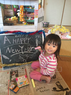テーブルの上に座っている小さな女の子の写真・画像素材[2130220]