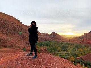 女性,1人,20代,ファッション,自然,風景,ショートカット,緑,黒,丘,黒髪,人物,人,旅,ブーツ,地面,コーディネート,海外旅行,モロッコ,コーデ,赤土,ブラック,黒コーデ,長ズボン