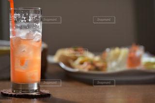 近くにオレンジ ジュースのガラスのの写真・画像素材[1663776]
