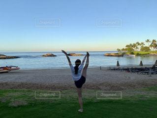 水域の近くの浜辺に立っている人の写真・画像素材[2130868]