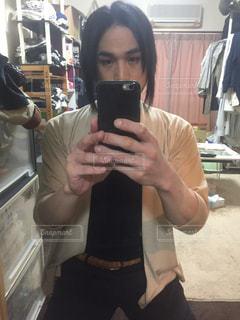 カメラにポーズを鏡の前で携帯電話を持っている人の写真・画像素材[1690483]