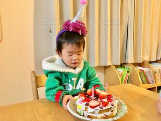 小さな男の子がケーキでテーブルに座っての写真・画像素材[1667810]