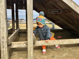 少し少年が座っている木製のフェンスの上にの写真・画像素材[1672320]
