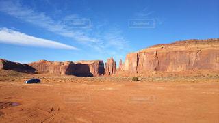 アメリカの荒野を走る青い車の写真・画像素材[1818759]