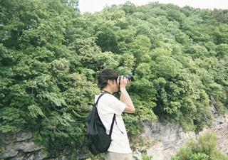 森の横に立っている人の写真・画像素材[1871014]