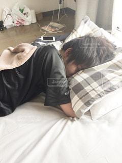 ベッドの上で横になっている人の写真・画像素材[1877612]