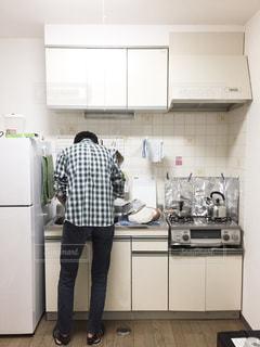 キッチンに立っている人の写真・画像素材[1877619]