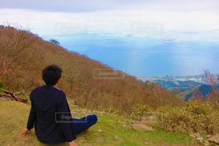 草の生いた丘の上に立っている男の写真・画像素材[2225838]