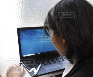 ラップトップ コンピューターの前に立っている人の写真・画像素材[1680144]