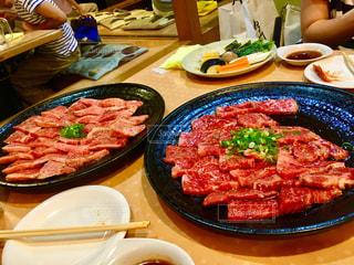 食品のプレートをテーブルに座っている人々 のグループの写真・画像素材[1660348]