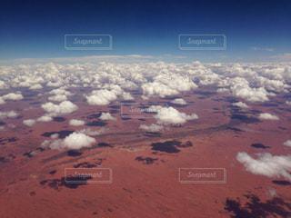赤い大地に青い空と羊さんみたいな雲。オーストラリアの空の上から。の写真・画像素材[1861200]