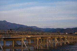背景の山が付いている水の体の上の橋の写真・画像素材[1667684]