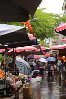 傘を持って通りを歩いている人々のグループの写真・画像素材[2174070]