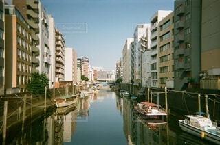 背景に都市がある水域の小さなボートの写真・画像素材[4806181]