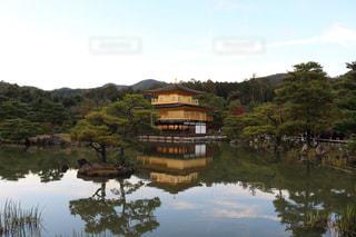 背景の金閣寺の水の体の横に川に沿って旅行ボートの写真・画像素材[1675558]