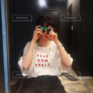 カメラにポーズ鏡の前に立っている人の写真・画像素材[1836886]