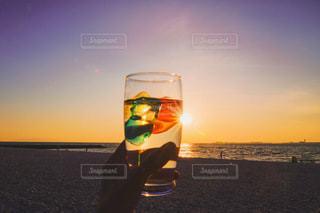ビーチでコップ一杯の水を持っている人の写真・画像素材[3560110]