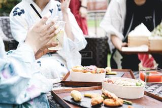 食べ物を食べるテーブルに座っている人々のグループの写真・画像素材[2312413]