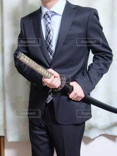 スーツとネクタイと刀を身に着けている男の写真・画像素材[1694067]