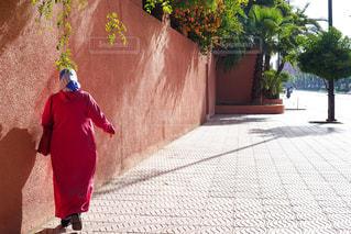 女性,屋外,ピンク,太陽,赤,後ろ姿,歩く,人物,背中,壁,人,文化,モロッコ,アフリカ,伝統衣装