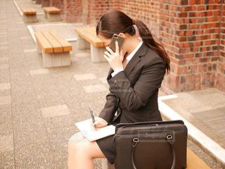 携帯電話で話しているベンチに座っている女性の写真・画像素材[1873754]