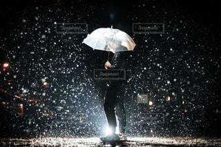 雨の中で傘を持っている男性の写真・画像素材[1694093]