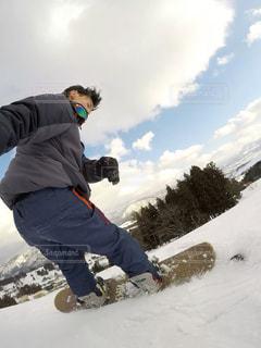 雪をスノーボードに乗る男覆われた斜面の写真・画像素材[1705250]