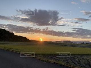 背景に夕焼けをした男の写真・画像素材[2424968]