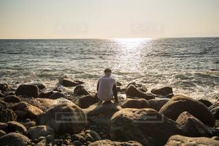 1人,自然,風景,海,空,屋外,太陽,哀愁,ビーチ,砂浜,夕暮れ,水面,海岸,水平線,岩,人物,背中,人,夕陽,眺め,海を眺める