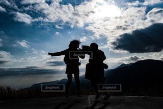 空には雲の丘の上に立っている人の写真・画像素材[1713644]