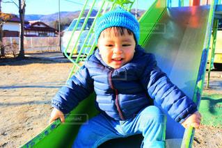 スライド上に座っている小さな男の子の写真・画像素材[1749497]