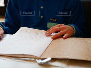 ラップトップを使用してテーブルに座っている人の写真・画像素材[1715557]