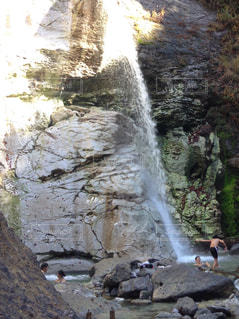 岩の横にある大きな滝の写真・画像素材[1027696]